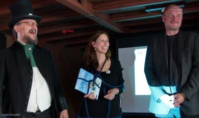 Program moderoval Alfréd Nobel alias Jiří Walker Procházka. Vedle něj stojí autoři: spisovatelka Klára Smolíková a ilustrátor Luděk Bárta. Fotila Hanina Veselá